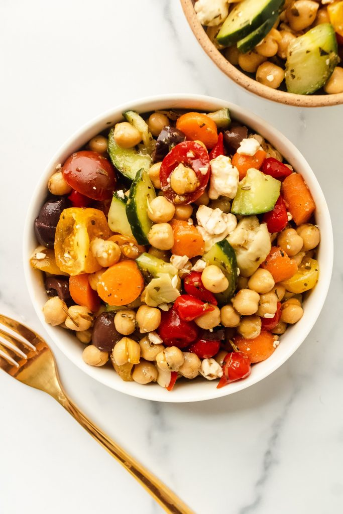 mediterranean chickpea salad with cucumbers, feta, tomatoes, olives, artichokes, and carrots