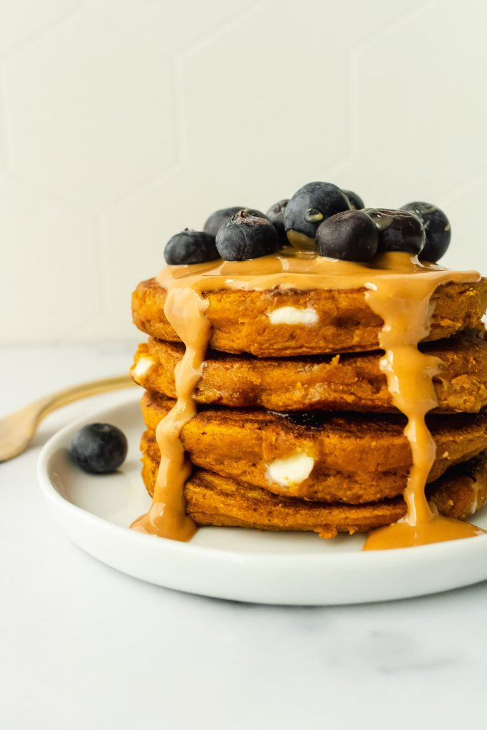 one bowl pumpkin pancakes with white chocolate chips and blueberries on top