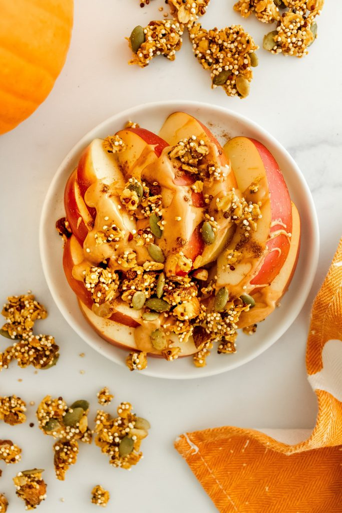 apples with peanut butter and healthy pumpkin granola on top