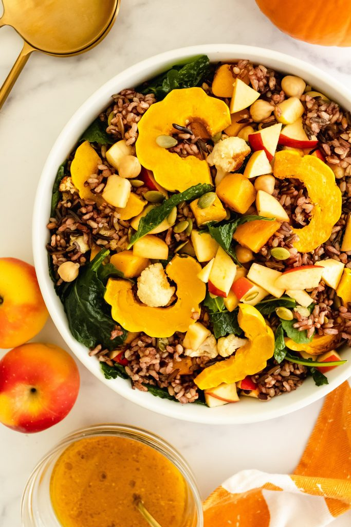 fall harvest bowl with squash, apples, delicata squash, kale, cauliflower, chickpeas, pumpkin seeds and wild rice