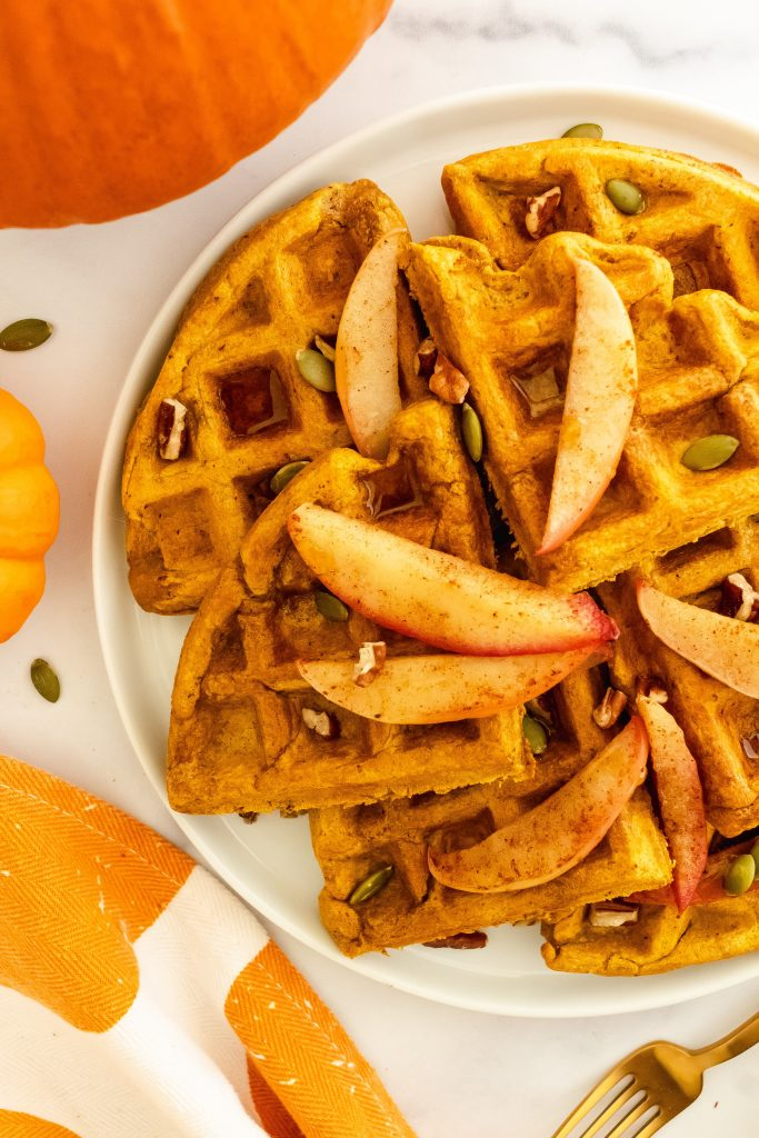 best fluffy whole grain pumpkin waffles with pecans, pumpkin seeds, and cinnamon apples on top