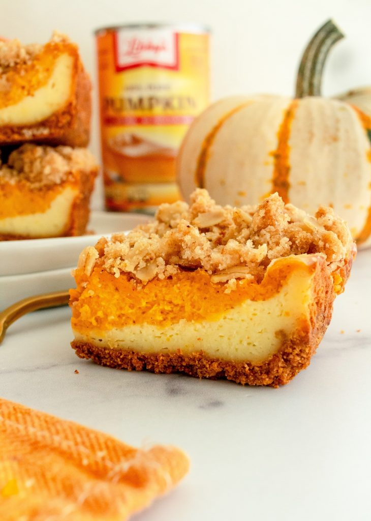 layered pumpkin cheesecake bar with streusel topping and graham cracker crust