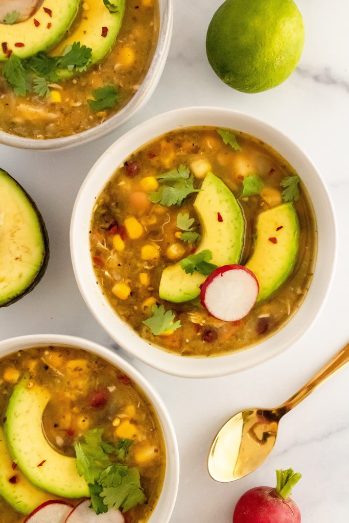 vegan roasted tomatillo soup with sliced avocado on top