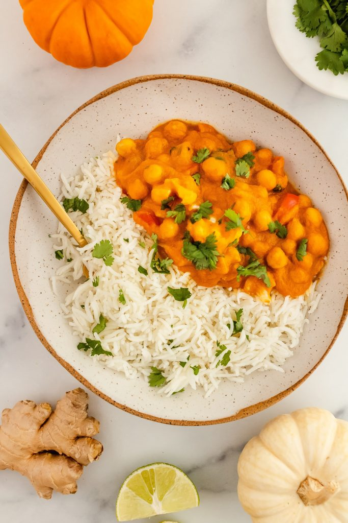 pumpkin chickpea curry with cauliflower and coconut milk topped with fresh cilantro on a bed of basmati rice